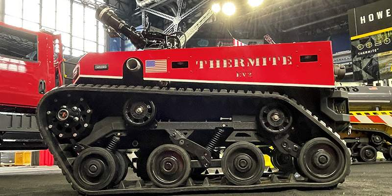 Thermite EV2 red vehicle at FDIC tradeshow, Howe & Howe products Big Dog and Thermite RS1 in background